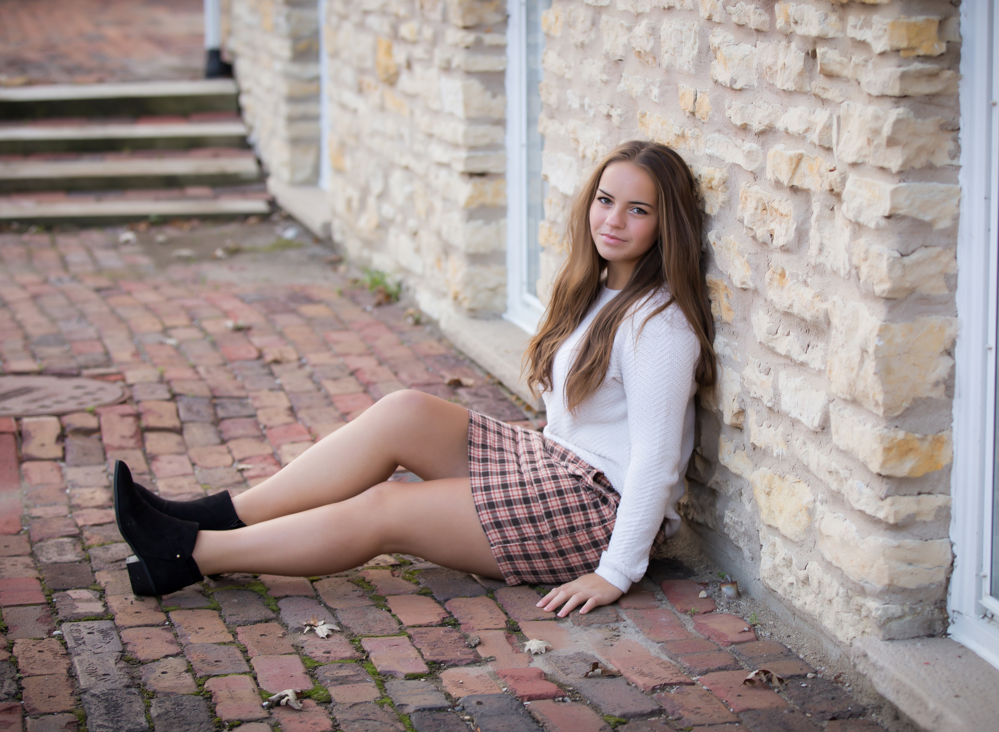 blonde-girl-in-plaid-skirt-sitting-and-leaning-against-wall