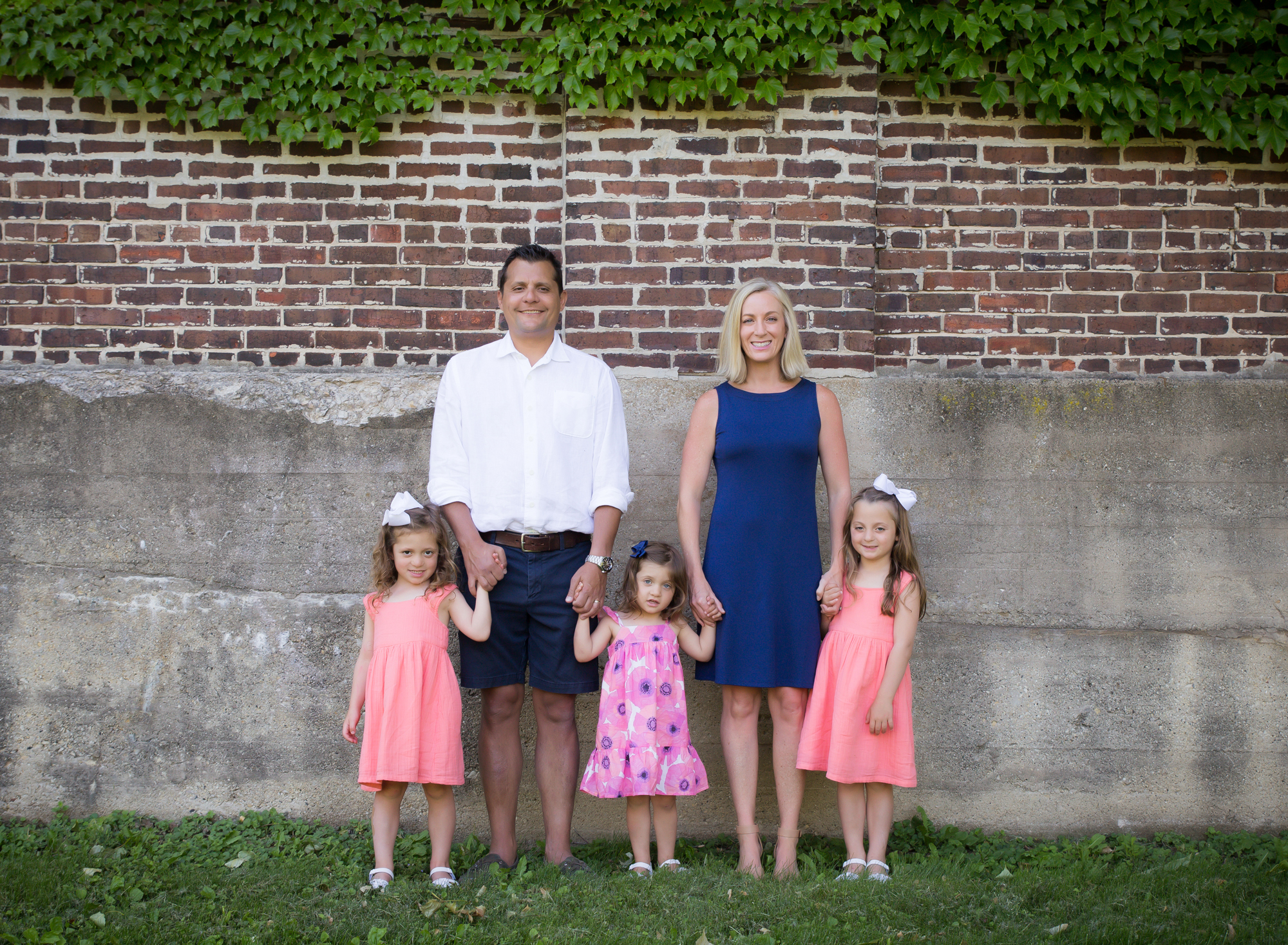family-of-five-holding-hands-in-front-of-red-brick-wall