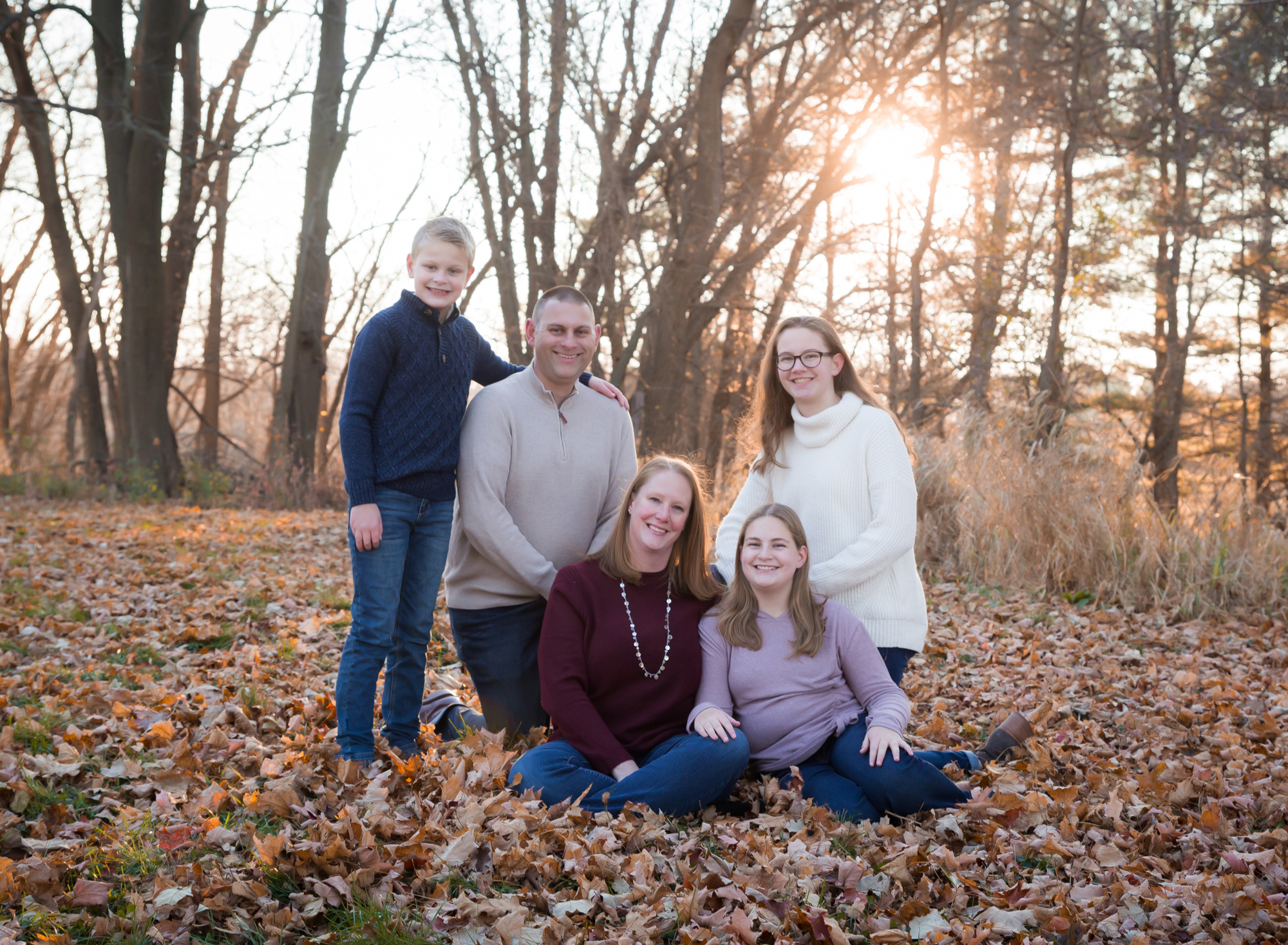 family-of-five-sitting-in-fall-leaves