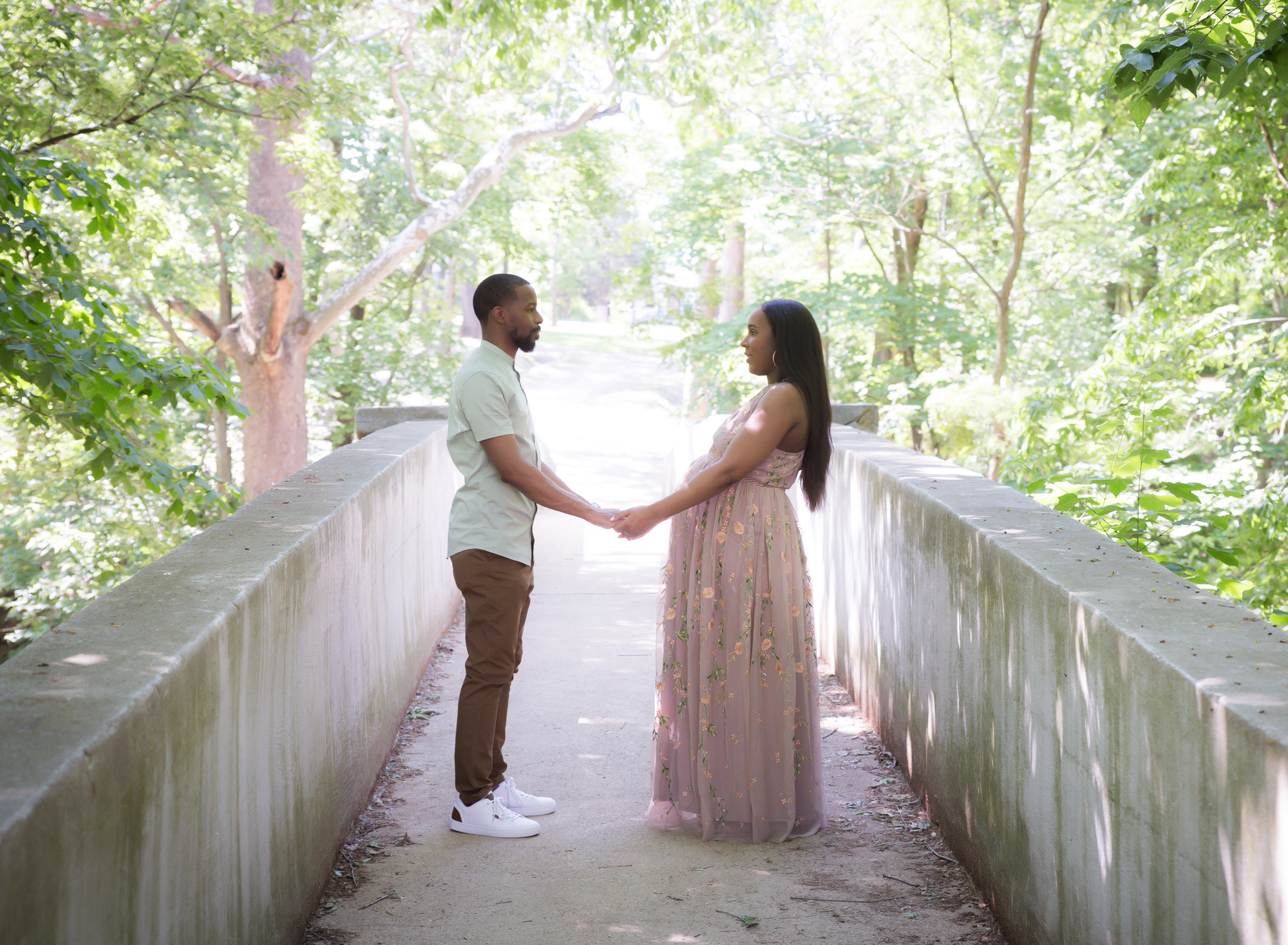 pregnant-couple-holding-hands-on-bridge-looking-at-eachother