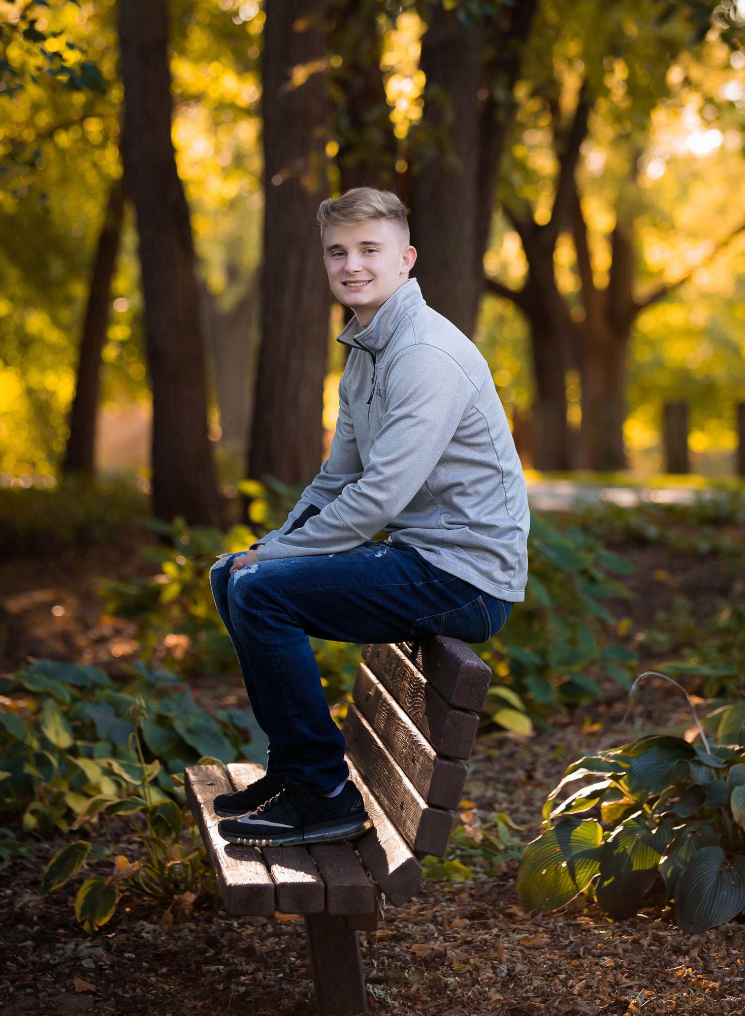 senior-boy-sitting-park-bench