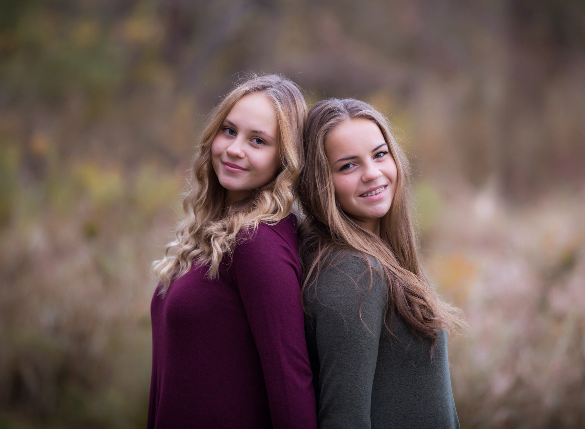 senior-sisters-leaning-back-to-back